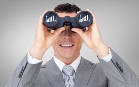 Composite image of businessman holding binoculars