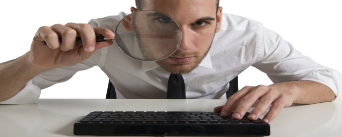 Businessman looks on the computer with a  lens
